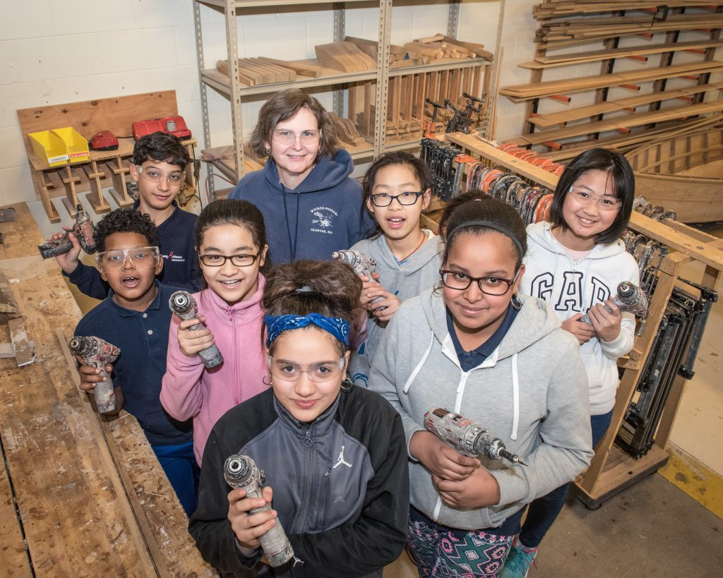 Smiling children wearing protective goggles hold power tools as an instructor looks on