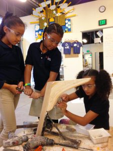 Three girls working on building a boat