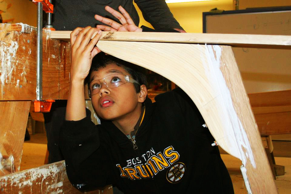 A boy measuring part of a boat he is building