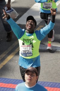 Joyous black teenager crosses finish line