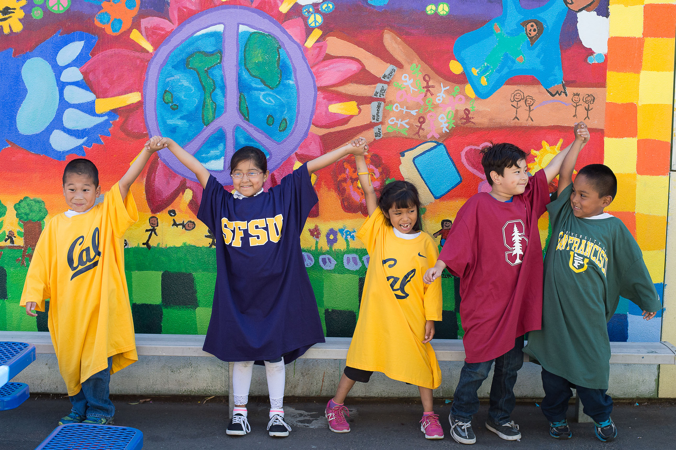 Small children wearing large college t-shirts