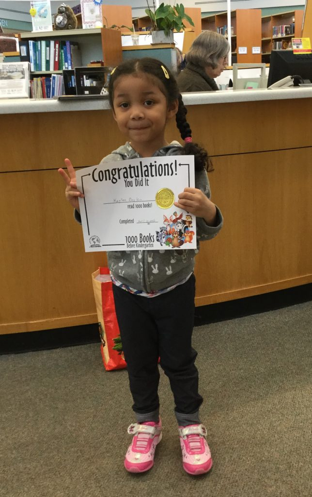 Little girl holds book she won for completing 1000 Books Before Kindergarten