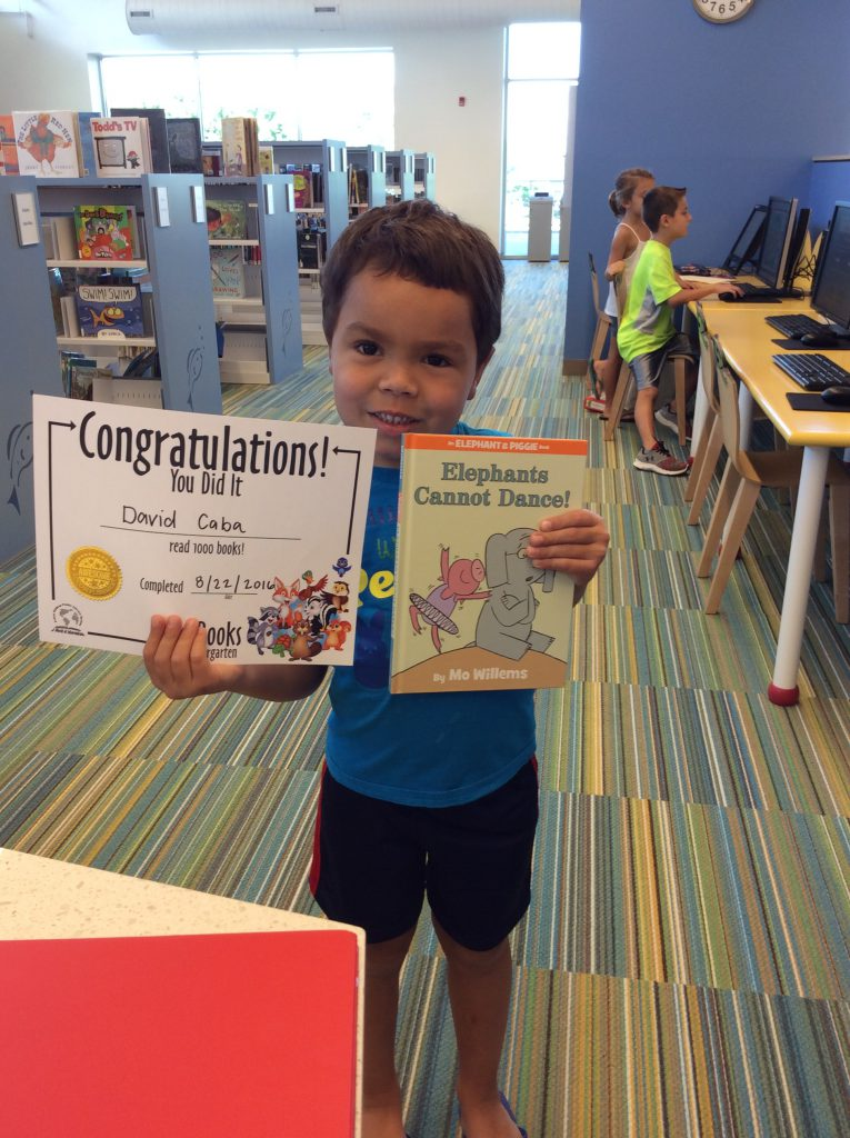 Little boy holds book she won for completing 1000 Books Before Kindergarten