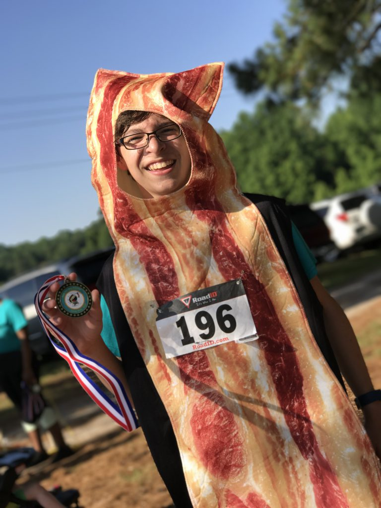 Contestant in bacon costume holding medal