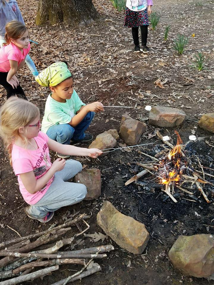 Girl Scouts toast marshmallows over a campfire