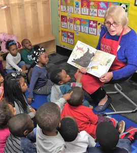 Children listen intently as a blond woman reads a storybook to them