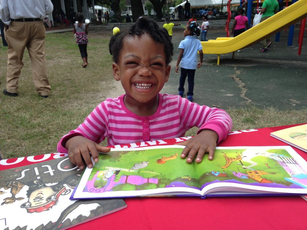 Grinning child looks at a storybook at a BEGIN WITH BOOKS presentation in a local park