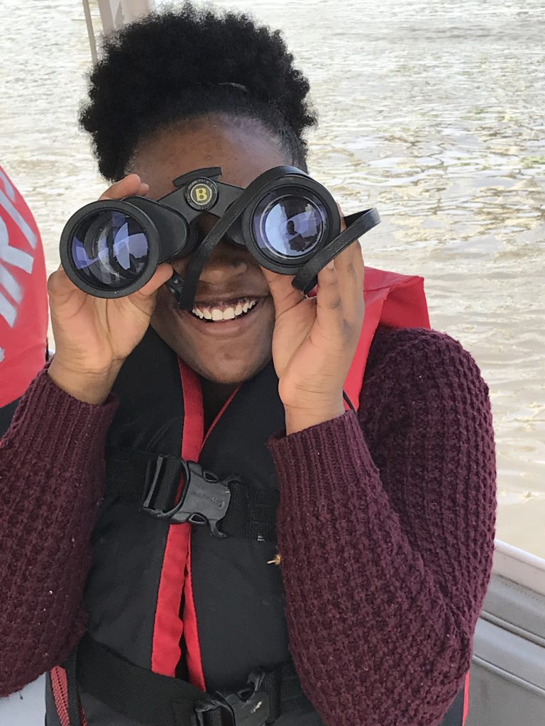 Smiling Green Works student looks through binoculars