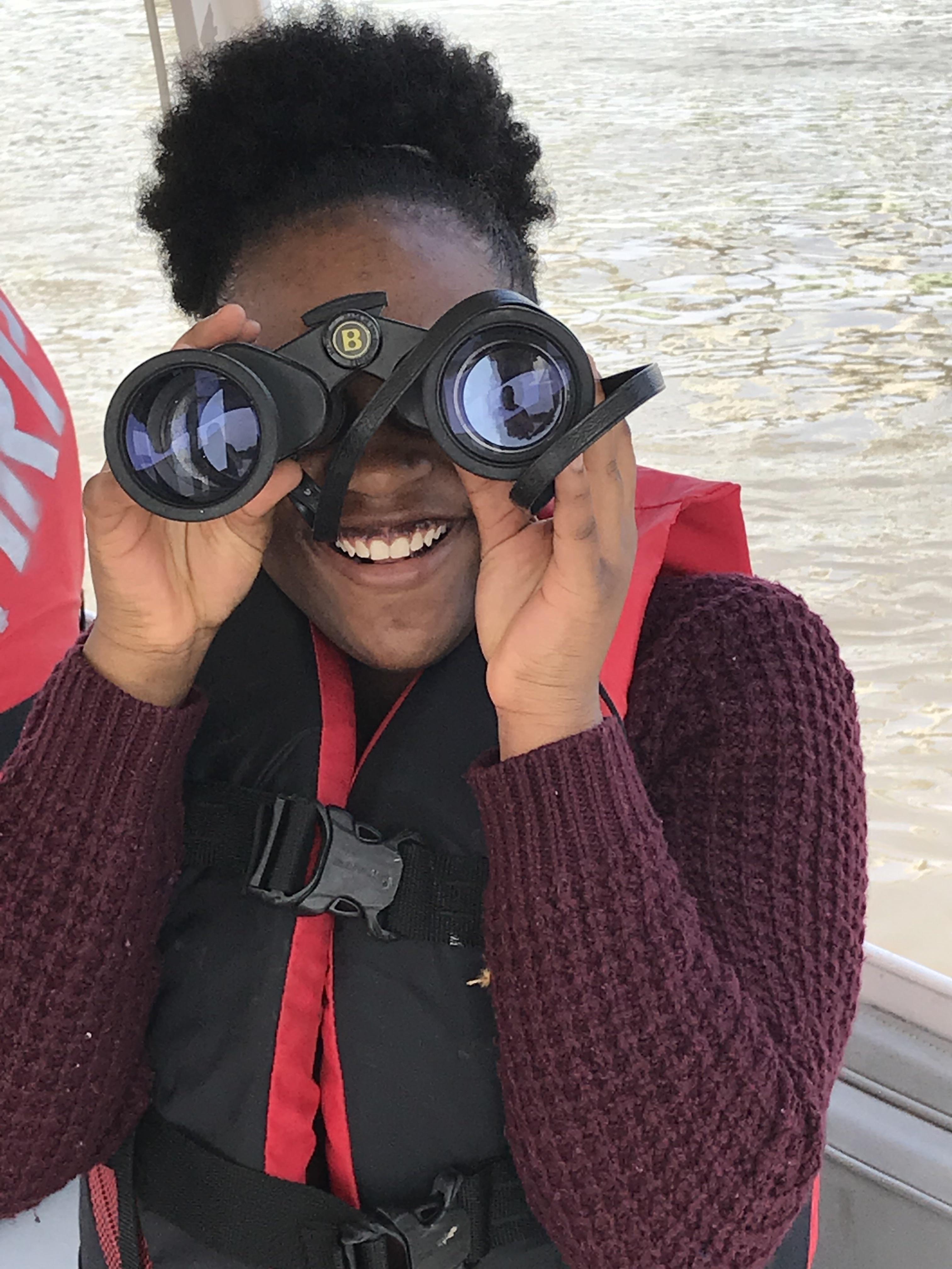 Smiling Green Works student looks through binoculars