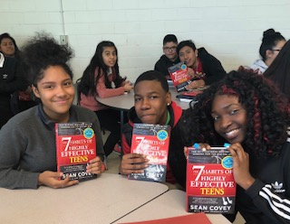 High school students smile on receiving book about the habits of success