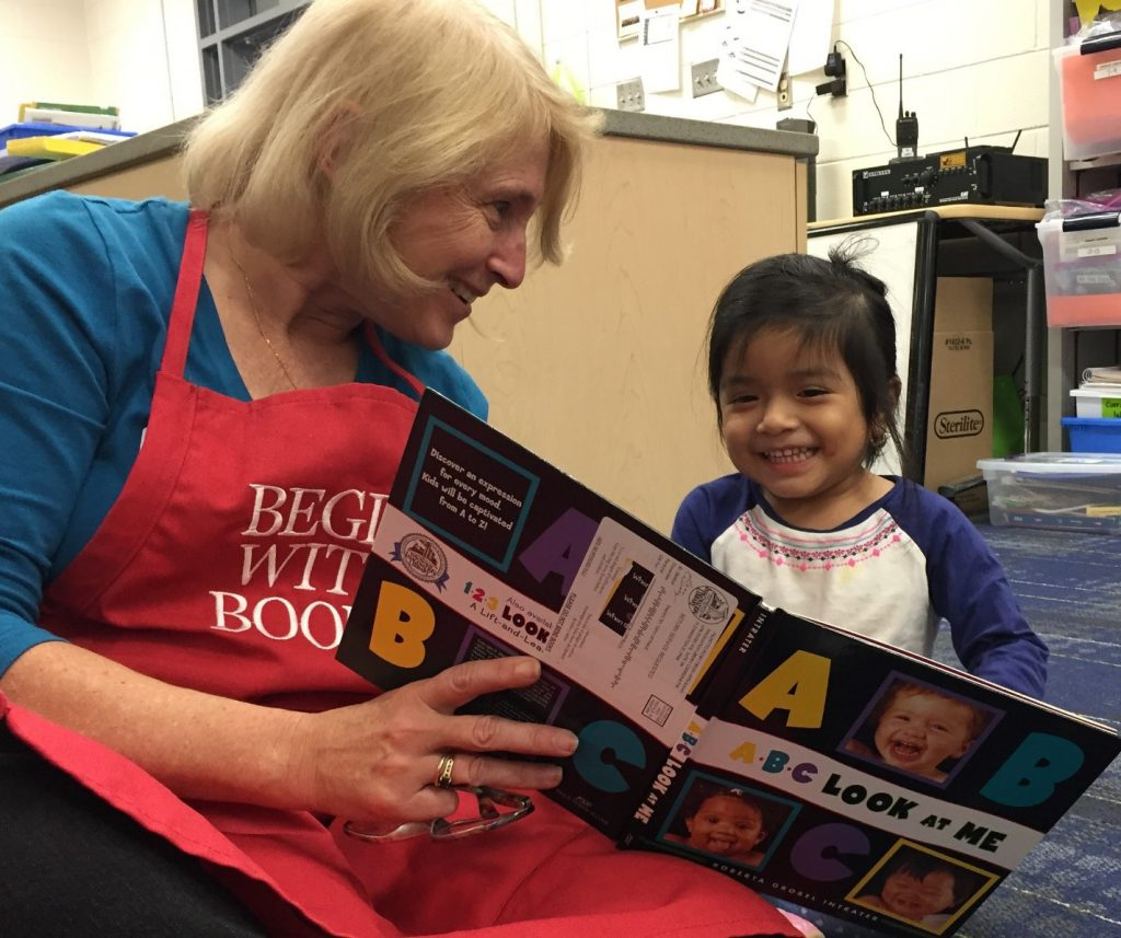 Smiling volunteer reads book to young child