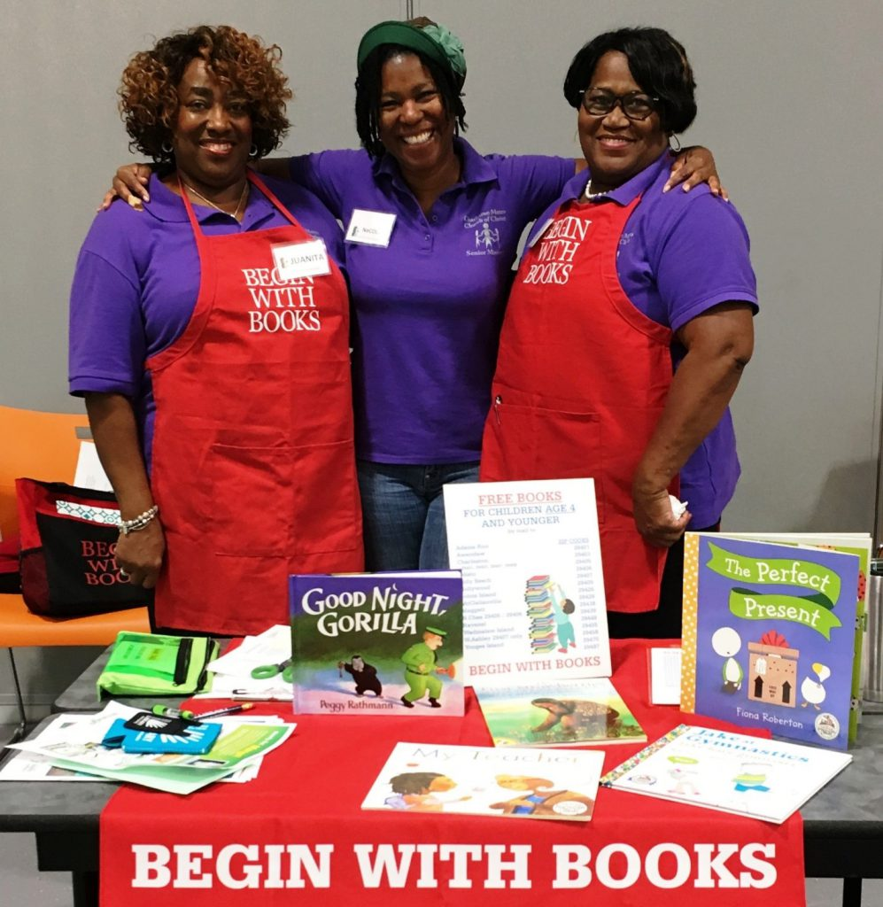 Three smiling BEGIN WITH BOOKS volunteers