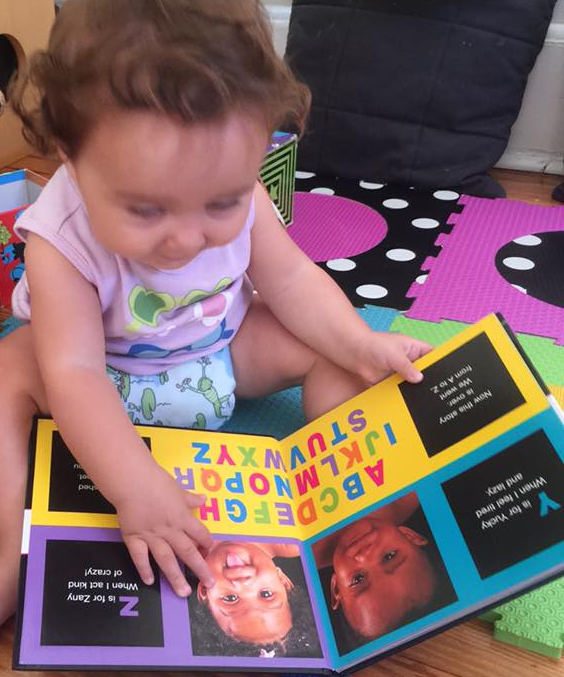 Toddler smiling while holding and reading book