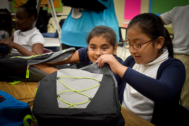 Girl checks out her new backpack filled with school supplies
