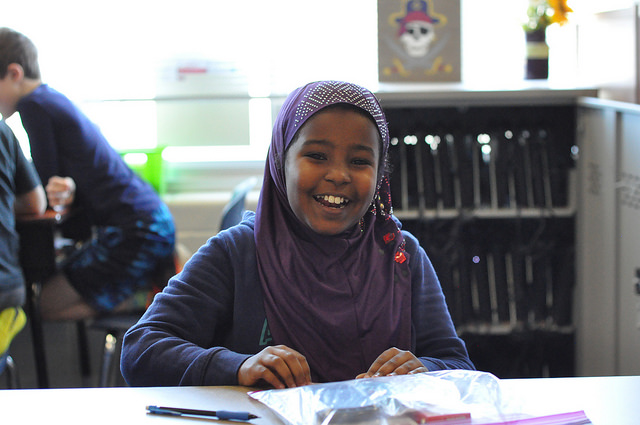 Girl in hijab is happy to receive school supplies
