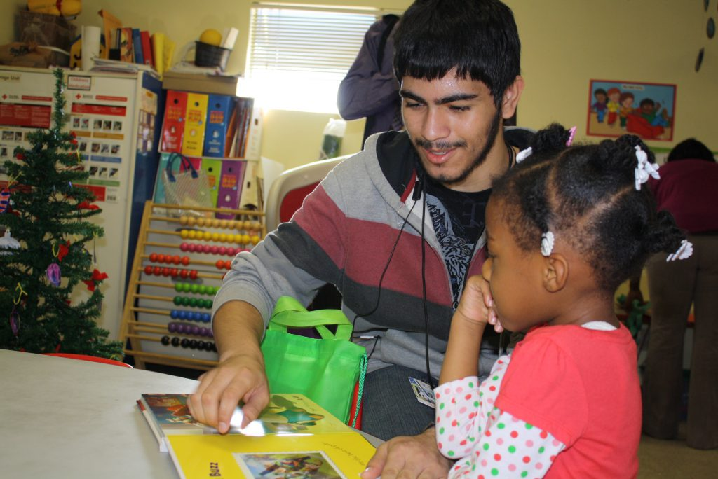 Young man looks at book with younger child