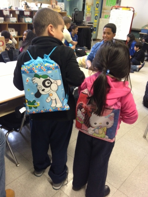 Two children show off their new backpacks