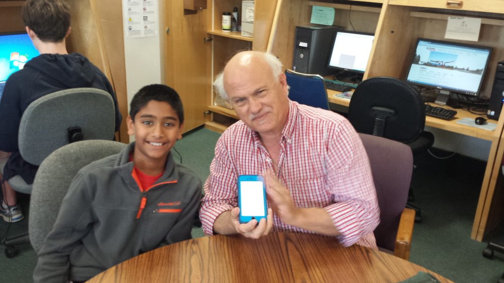 YouthSERVE young volunteer helps senior with his smartphone during Senior Tech Day
