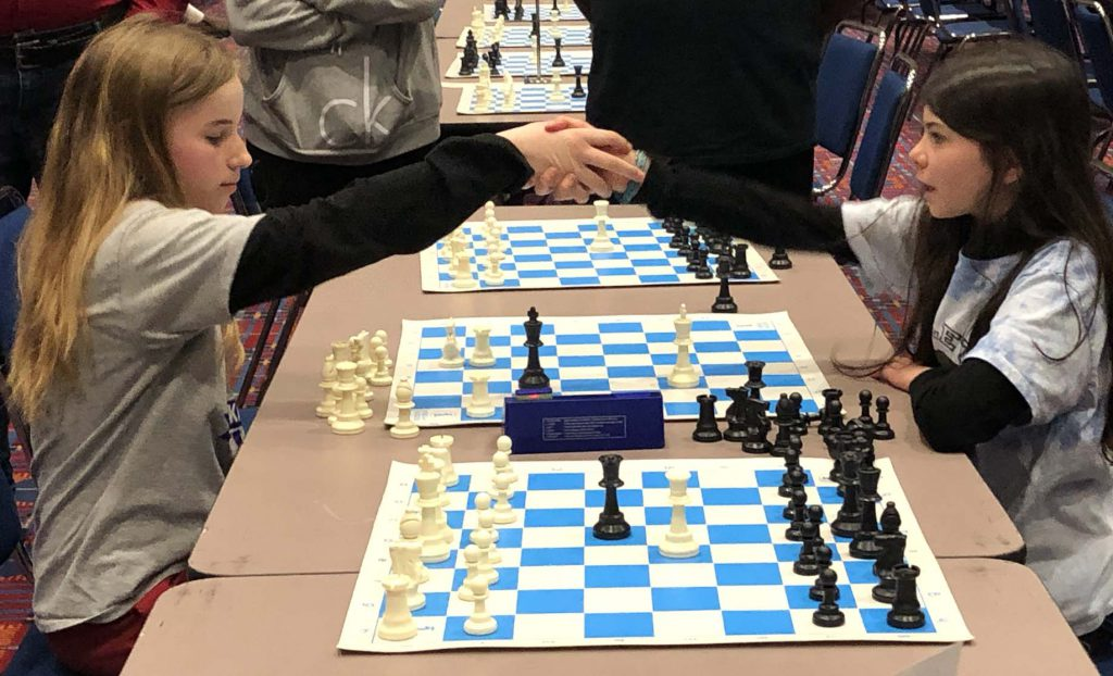 Girls shake hands during chess tournament