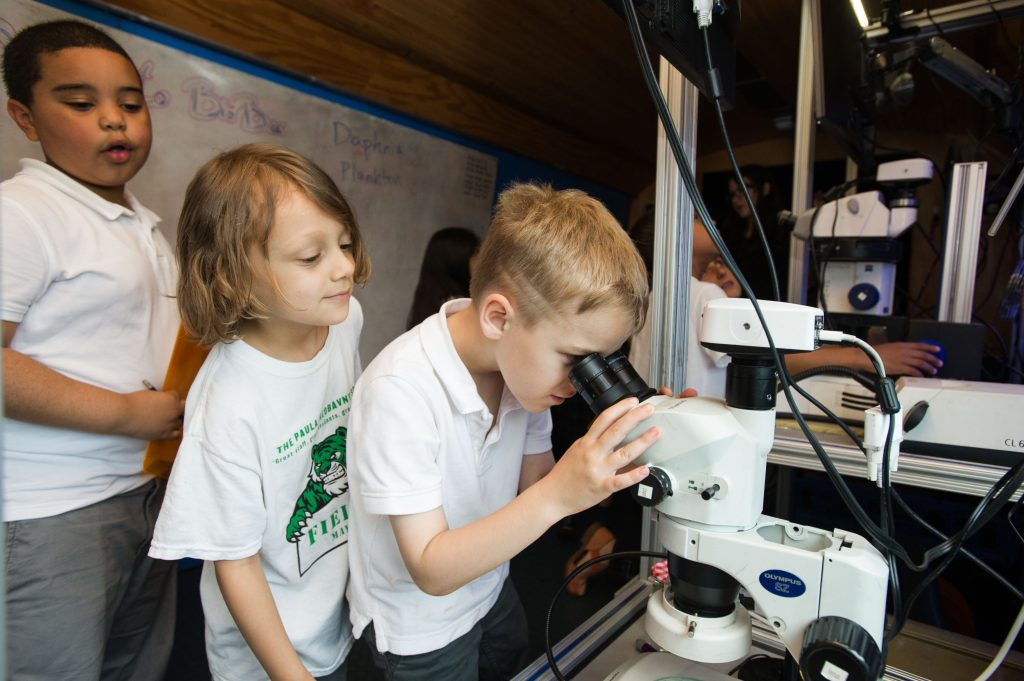 Taking turns looking into a microscope aboard BioBus