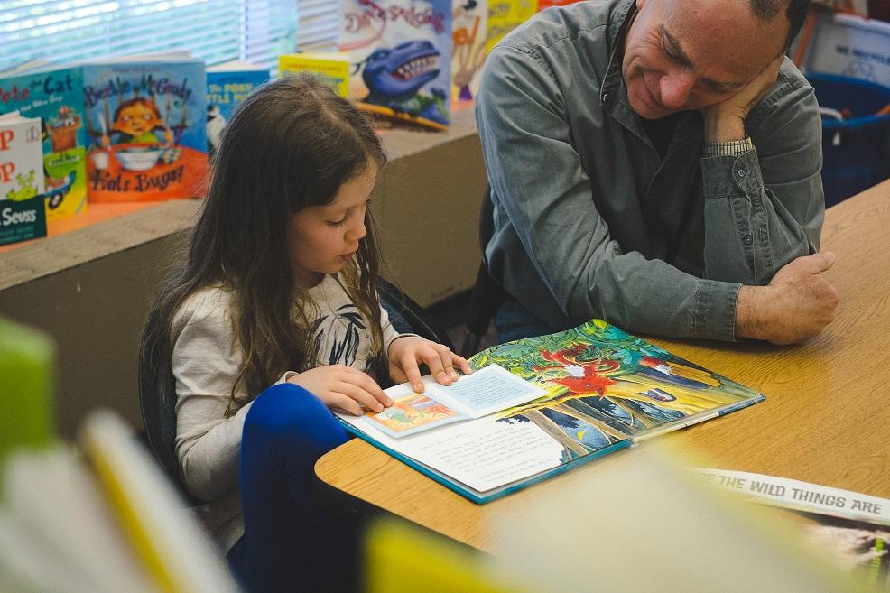 SMART volunteer listens to young girl read