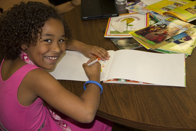 Smiling Girl engaged in SMART reading activity