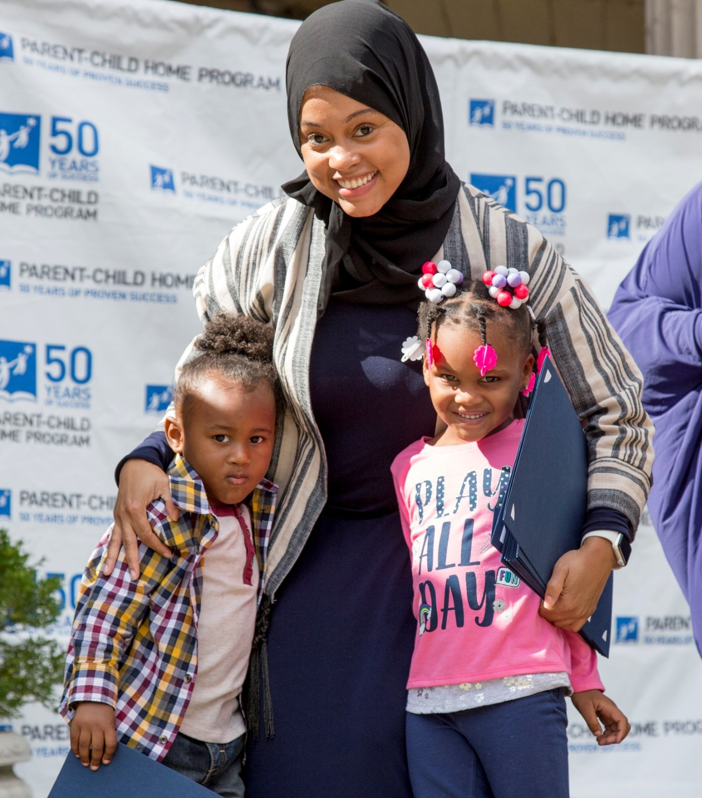 Mother in hijab reads to two children (Parent-Child Home Program)