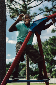 Smiling young black man climbs jungle gym