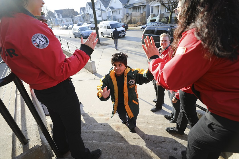 A young Philadelphia student is greeted on his way into school by AmeriCorps volunteers