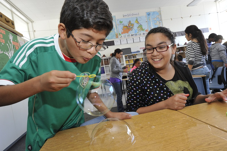 Aim High student blow bubbles as part of science experiment