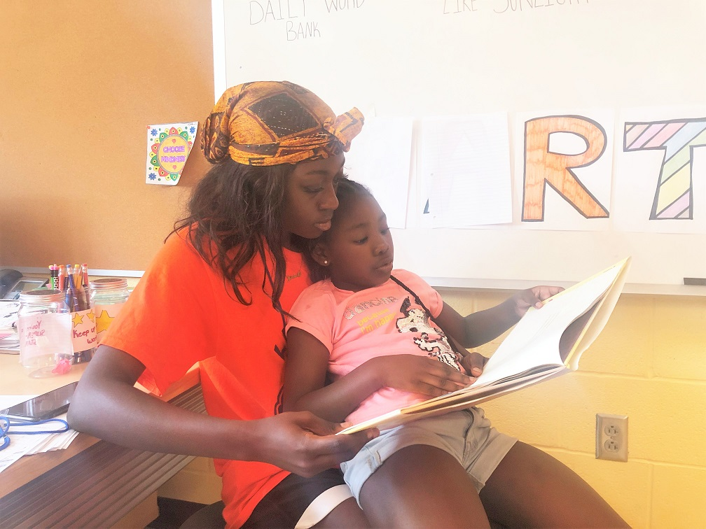 LEAP mentor reading and cuddling with her LEAP mentee