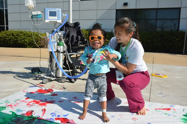 Smiling young patient with Ranken Jordan volunteer