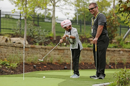 Young man plays golf at Ranken Jordan Pediatric Bridge Hospital