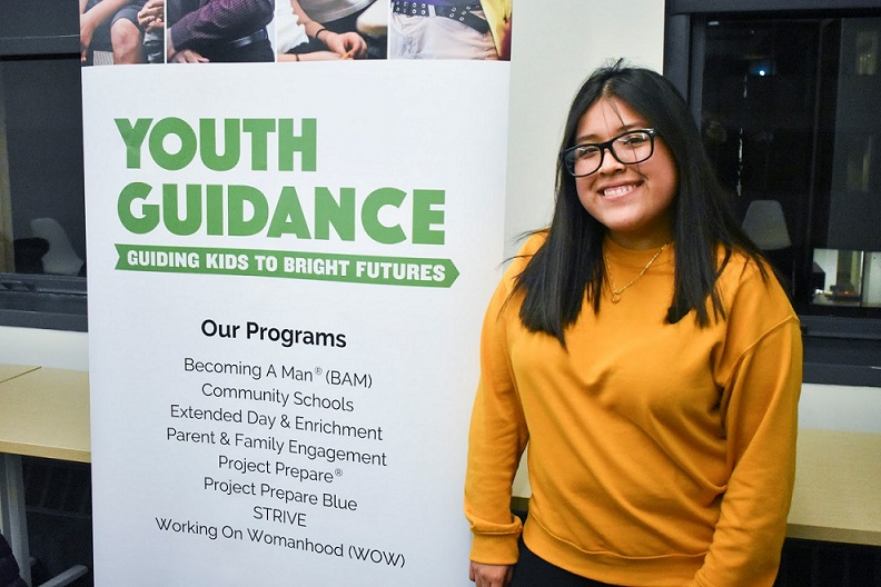 Smiling student next to poster listing Youth Guidance programs