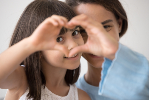young girl makes heart with two hands, as smiling guardian ad litem looks on