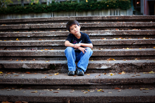 boy sits alone on steps