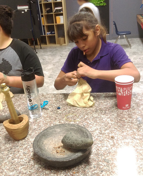 EOBA participants work with mortar and pestle