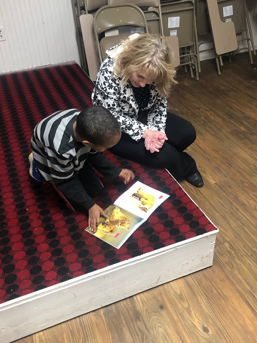 Volunteer helps young PFSS student with his reading