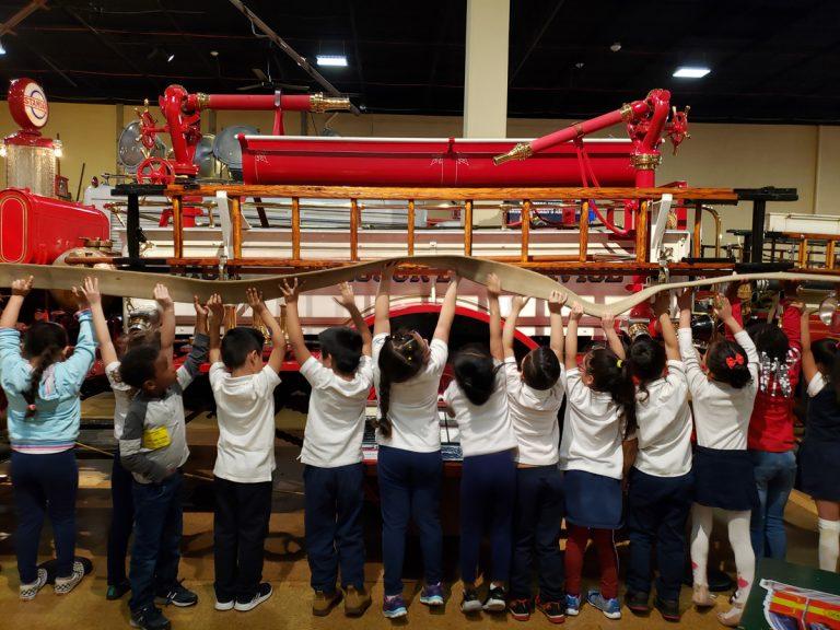 Highlandtown school children work to raise up a fire hose
