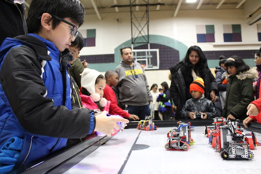 young boy races homemade robot during a STEM Night