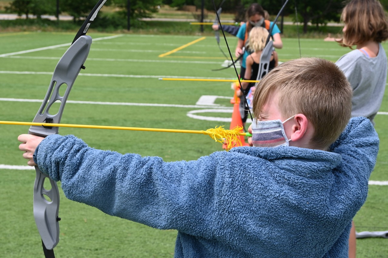 young blonde boy practices archery at the Y
