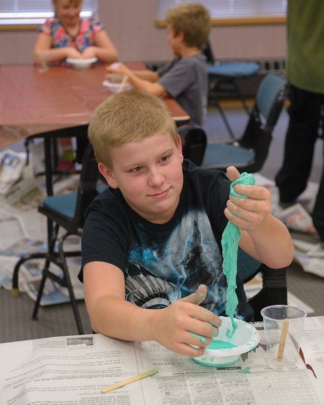 Boy plays with homemade slime during activity hour at the Jefferson County Public Library, supported by the Jefferson County Library Foundation