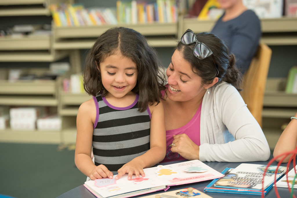 Smiling young girl reads to encouraging mother in library