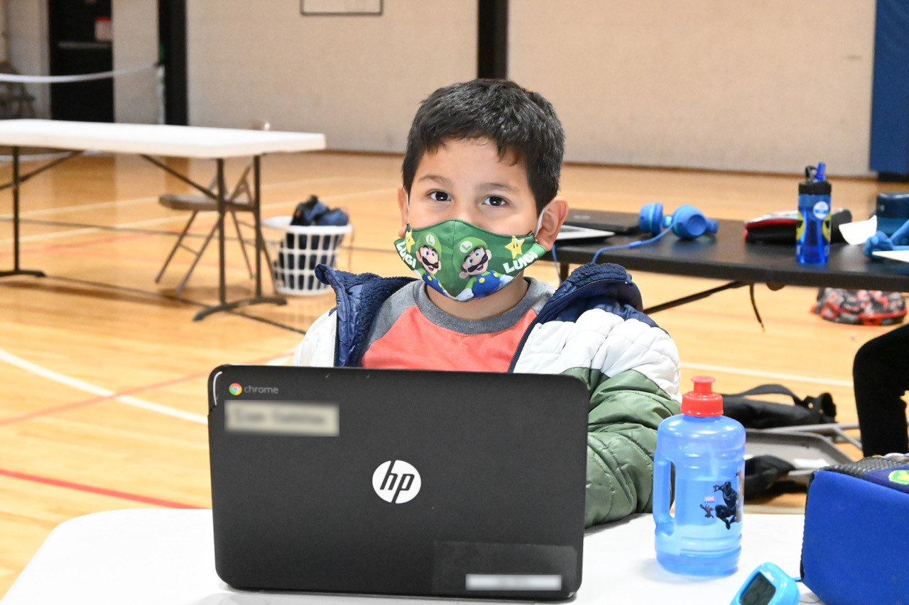 masked young man does homework at the Y