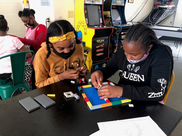 Female Urban Scholars Academy participants build with lego in the after school Homework Club