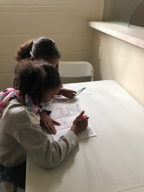 Urban Scholars Academy mentor and mentee do worksheet together