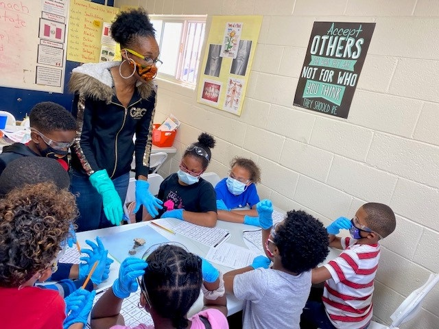 Urban Scholars Academy teacher works with students in the classroom