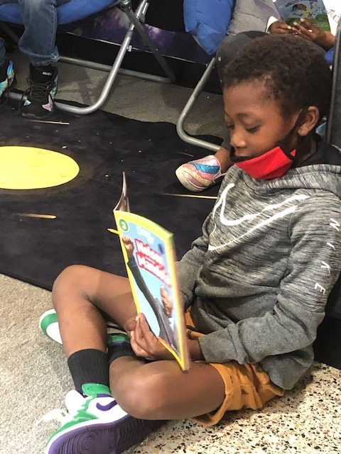 Urban Scholars Academy youngster reads book