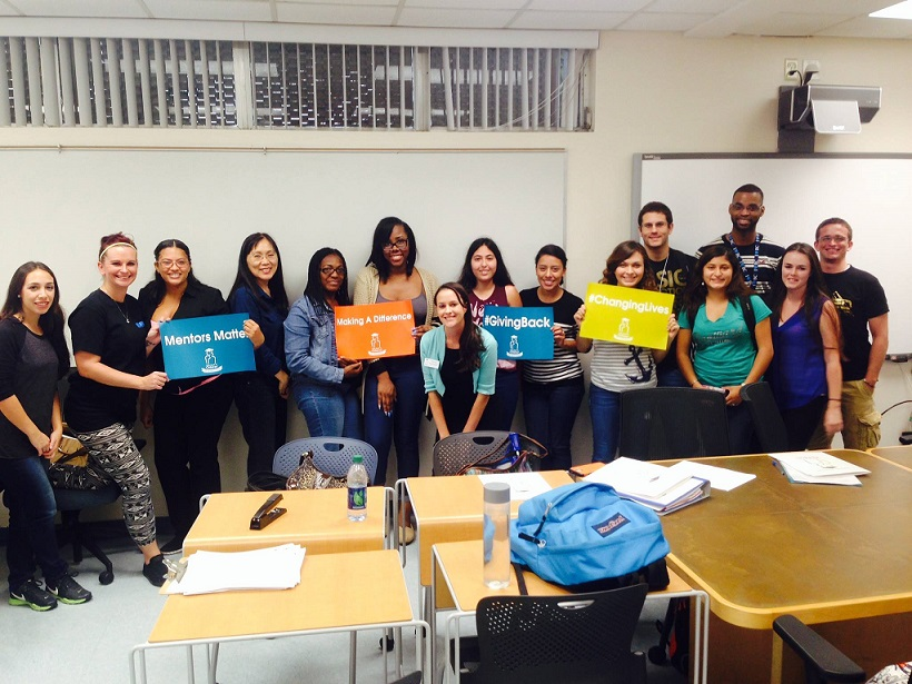 Take Stock in Broward participants in group photo hold up signs describing their educational and career goals.