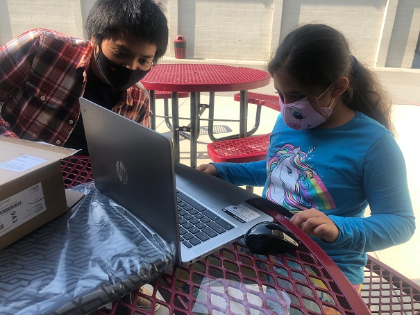 Boy and girl collaborate on homework over laptop at Mid-Peninsula Boys & Girls Club